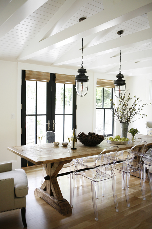 Light-filled modern farmhouse dining area with rustic wood table and white ceilings.