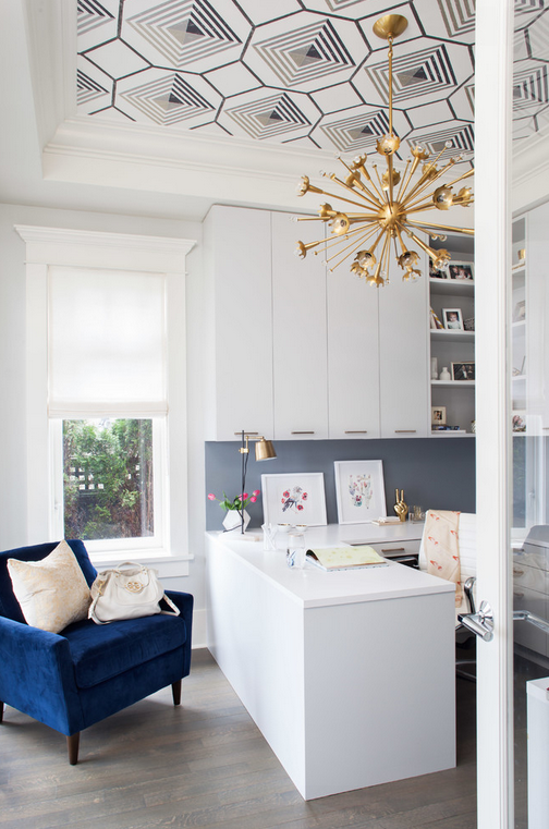 Amazing home office with graphic ceiling and gold accents and navy chair.