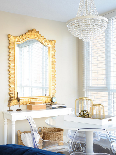 A perfect dining spot--lucite chairs, lovely chandelier, gold accents.