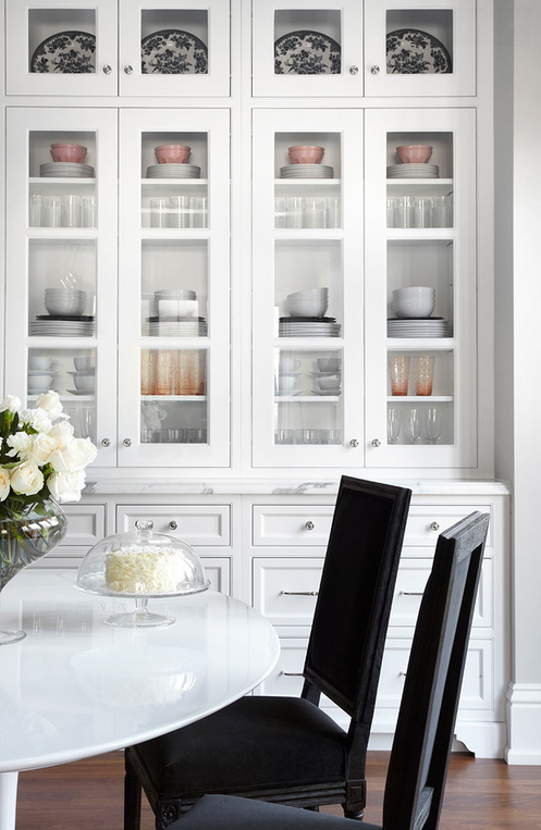 Glass front cabinets with beautiful dishware displayed within.