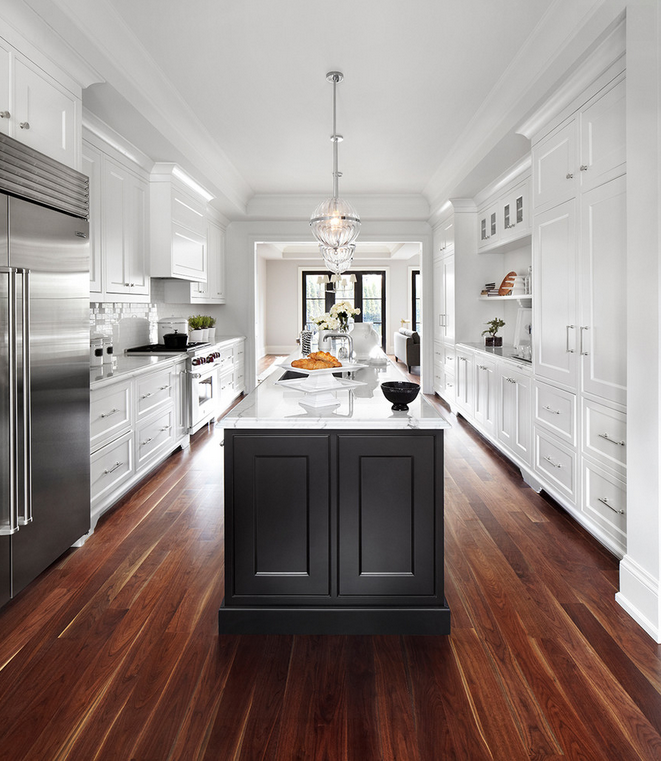 Striking white kitchen with dark wood floors.