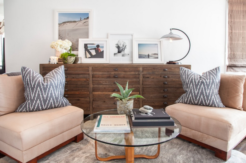 Beach house living room with organic design elements, rustic wood chest of drawers, uniform white frames.