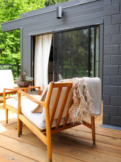 Black exterior brick never looked so good as it does paired with this wood patio set.