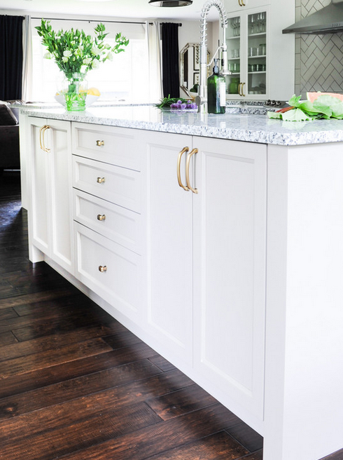 Kitchen by 2e designs with brass hardware, white island, and dark wood floors.