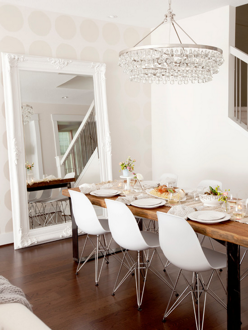 Gorgeous and serene dining space with beautiful beaded light fixture, large leaning mirror, modern white chairs, and subtle polka-dotted walls.