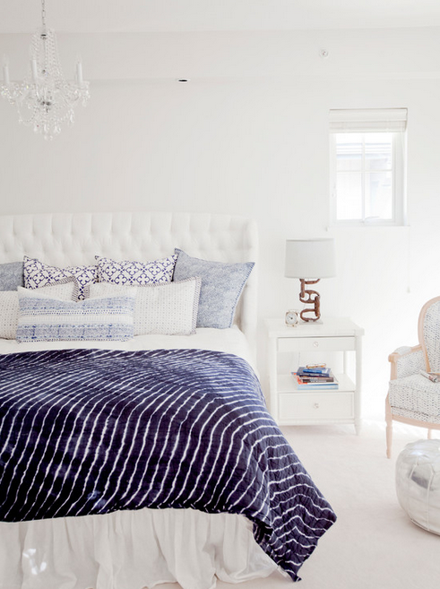 Beautiful white bedroom with tufted headboard and navy blue accents.