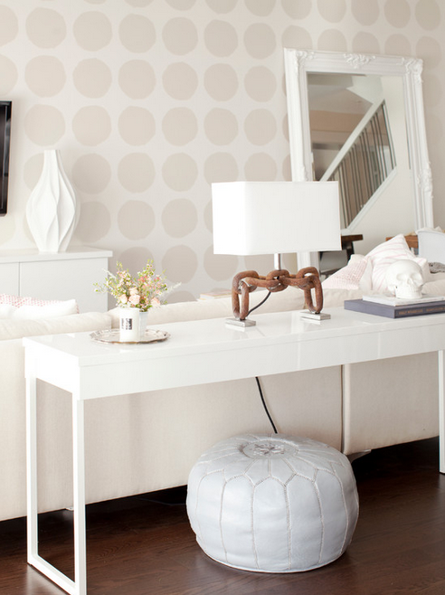 Subtle polka-dotted walls and serene white palette.