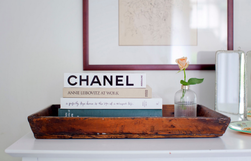 sweet vignette: rustic wood tray, a stack of books, and a single rose.