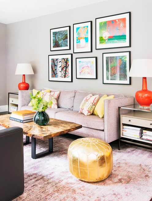 Framed art, bright colored lamps, dusty rose sofa, rustic wood coffee table, and gold pouf.