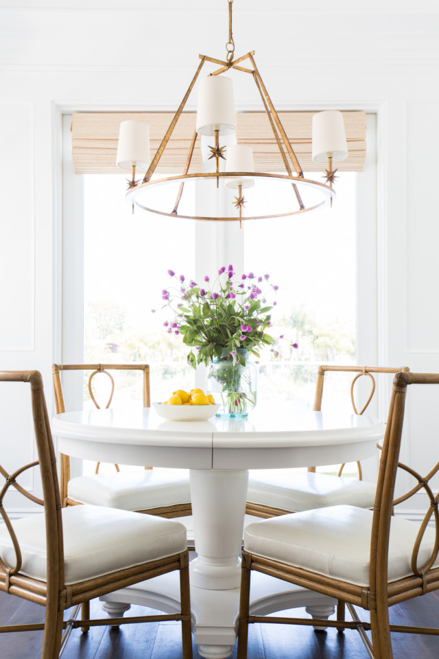 Dining area with bamboo chairs and a stunning brass light fixture by Studio McGee