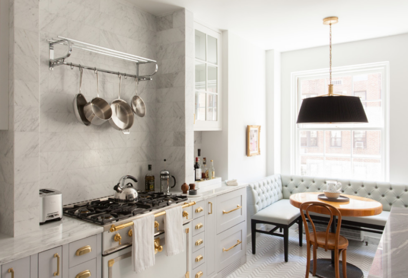Gorgeous kitchen with herringbone floors, gold fixtures and gray cabinetry.