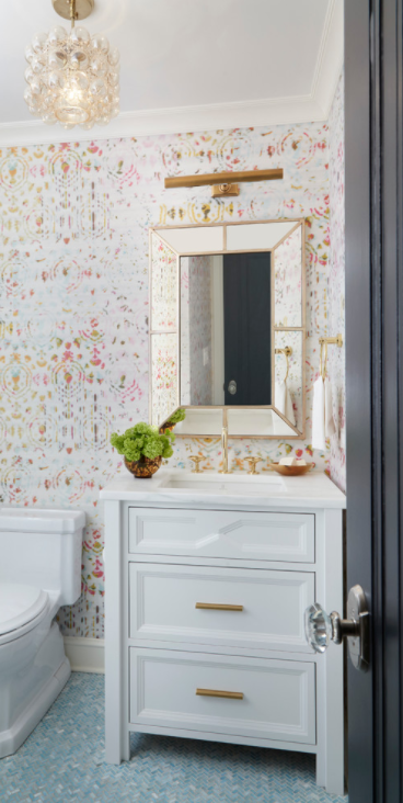 Pink and gold girl's bathroom boasts a beveled mirror mounted on a wall covered in Kandy Brit Pop Wallpaper over a white washstand accented with gold pulls and a white quartz countertop fitted with a polished brass gooseneck faucet illuminated by a brass picture fixed over the mirror and Jamie Young Small Cici 3 Light Drum Pendant hung in the center of the room over blue herringbone floor tiles.