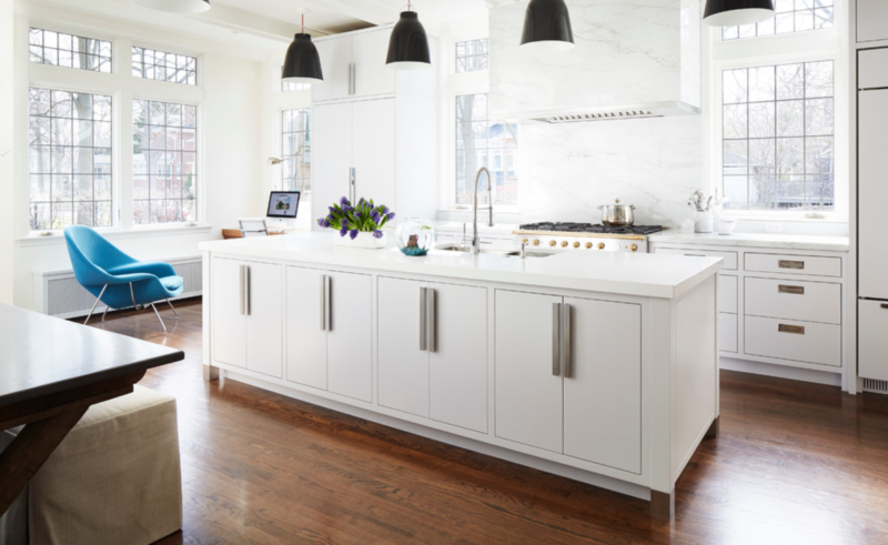 Modern white kitchen boasts black industrial pendants hung over a a white island topped with inset flat faced cabinets with satin nickel pulls and a white marble countertop fitted with a stainless sink and a polished nickel gooseneck .