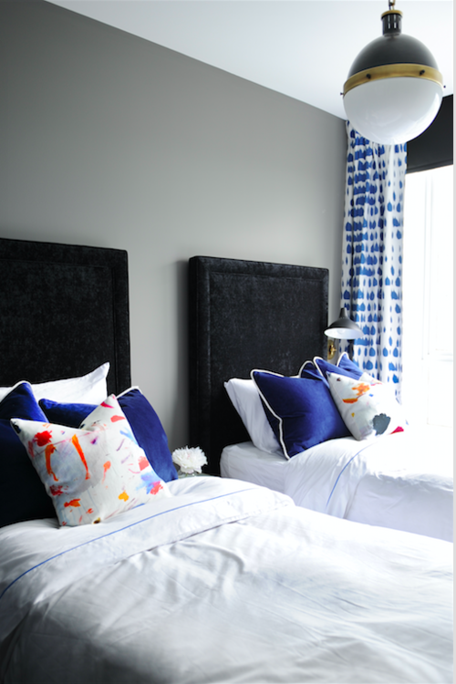 An easy yet sophisticated take on twin beds. The black, velvet headboards are balanced out with whimsically patterned curtains and throw pillows.