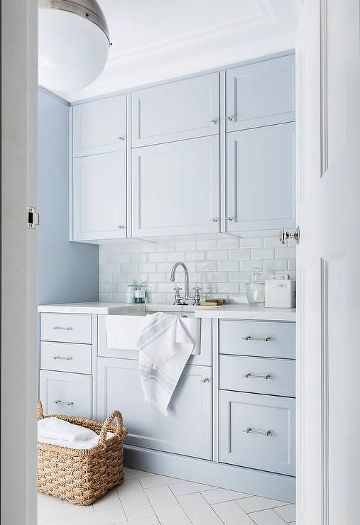 Seriously dreamy laundry room design. Blue cabinets, beautiful tile, stunning fixtures.