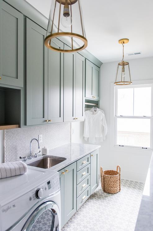 Seriously dreamy laundry room design. Mint cabinets, beautiful tile, stunning fixtures.